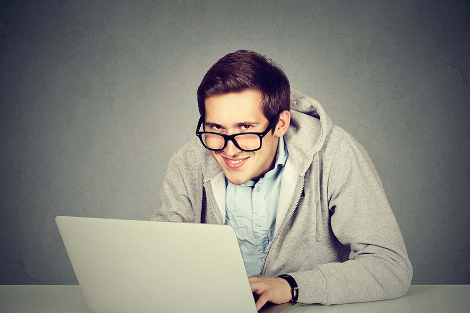 Homme assis devant sont ordinateur portable regardant vers nous Plug and Pulse