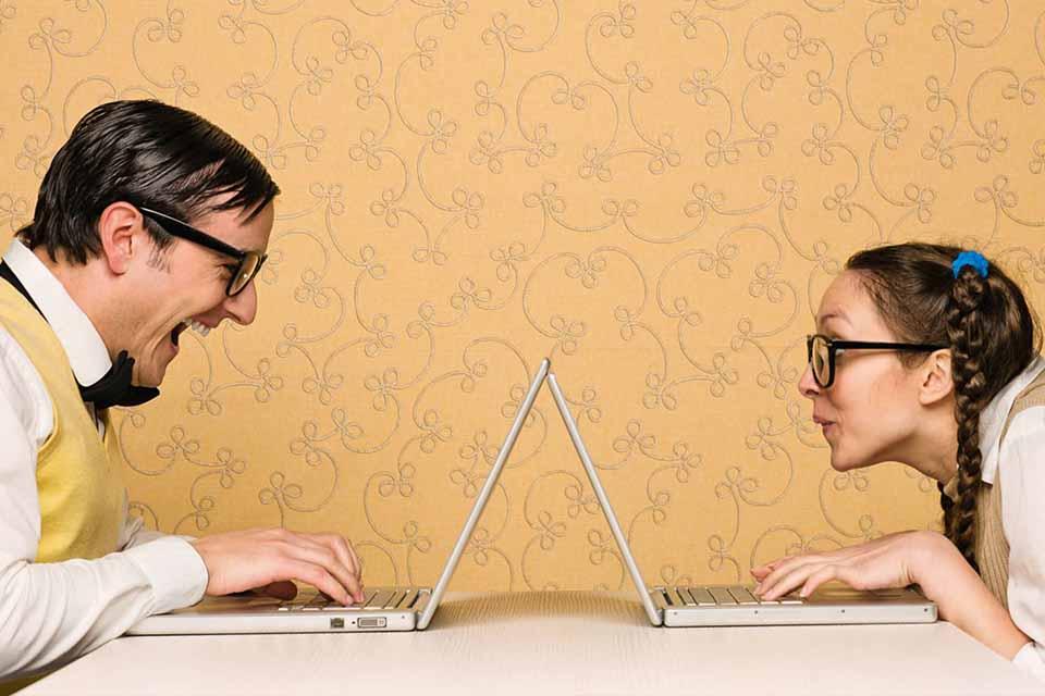 Un homme et une femme face à face travaillant sur leurs ordinateurs portables Plug and Pulse