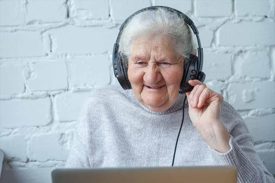vieille dame face à ordinateur avec casque pour formation plug and pulse